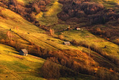 A beautiful autumn rural landscape with lonely houses, beautiful hills and a horse. Stock Photos