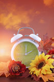 Autumn Fall Daylight Saving Time Clock Concept. Autumn daylight saving time concept with green clock on natural wood table with sunset sky background, and added royalty free stock images