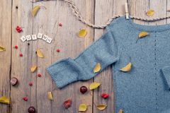 Autumn fall flat lay, top view. Warm knitted sweater, Fall Leaves, chestnuts, rowan berry and pumpkin with  inscription  `autumn` Royalty Free Stock Images