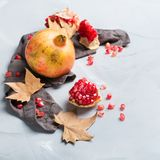 Harvest fall autumn concept. Ripe juicy pomegranate. Autumn fall harvest concept. Ripe juicy pomegranate on a cozy kitchen table stock image
