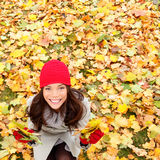 Autumn / Fall leaves background with woman happy. Looking up sitting on autumn leaves in colorful fall forest foliage. Beautiful girl with copy space. Mixed stock images