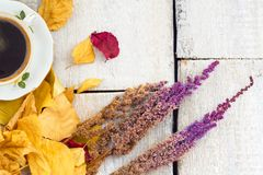 Autumn, fall leaves, hot steaming cup of coffee and flowers on wooden table background. Seasonal, morning coffee, sunday relax and Royalty Free Stock Images