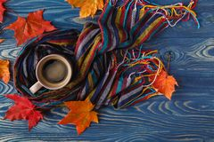 Autumn, fall leaves, hot steaming cup of coffee and a warm scarf Royalty Free Stock Image