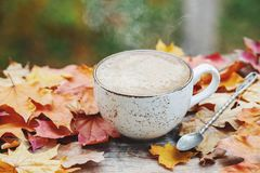 Autumn, fall leaves, hot steaming cup of coffee on wooden table background. Seasonal, morning coffee, Sunday relaxing and still li. Fe concept. With copy space stock photography