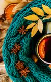 Autumn, fall leaves, hot steaming cup of glint wine. And a warm blue scarf on wooden table background. Seasonal, autumnal hot wine, Autumn relaxing and still stock images