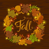 Autumn fall leaves wreath with festive light bulb garland. And handwritten text Stock Photos