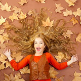 Autumn fall little blond girl on dried tree leaves Stock Photo
