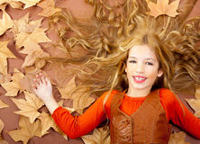 Autumn fall little blond girl on dried tree leaves Royalty Free Stock Photography