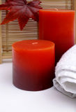 Autumn Fall Spa. Red and orange autumnal coloured candles with white towel for a relaxing spa or bathroom Royalty Free Stock Photos