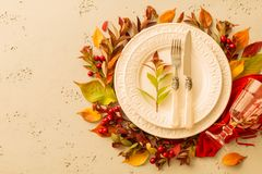 Autumn fall or thanksgiving moody table setting design. Autumn fall or thanksgiving table setting design captured from above top view, flat lay. White plate royalty free stock photo
