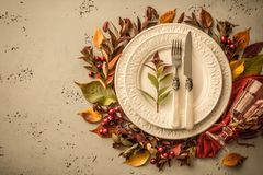 Autumn fall or thanksgiving moody table setting design. Autumn fall or thanksgiving table setting design captured from above top view, flat lay. White plate stock photography