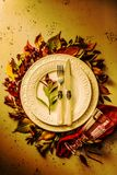 Autumn fall or thanksgiving moody table setting design. Autumn fall or thanksgiving table setting design captured from above top view, flat lay. White plate stock photo