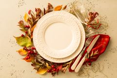 Autumn fall or thanksgiving table setting design. Captured from above top view, flat lay. Empty white plate, glass, cutlery and decorations colorful leaves stock photo