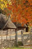 Autumn, fall village. Park in Ukraine. image of an old house with a straw on the roof. Around the house is a wicker fence stock photography