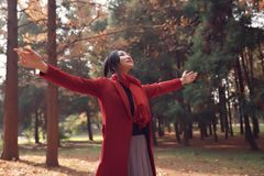 Autumn / fall woman happy in free freedom pose. With arms raised up towards the sky with smiling cheerful, elated expression of happiness. Beautiful girl in Stock Images