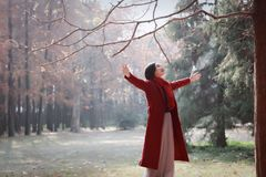 Autumn / fall woman happy in free freedom pose. With arms raised up towards the sky with smiling cheerful, elated expression of happiness. Beautiful girl in Stock Image