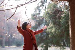 Autumn / fall woman happy in free freedom pose. With arms raised up towards the sky with smiling cheerful, elated expression of happiness. Beautiful girl in Royalty Free Stock Photo