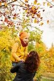 Autumn Family felice nel parco di caduta all'aperto Immagine Stock