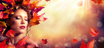 Autumn fantasy girl - Beauty fashion model. With red leaves and sunlight Stock Photography