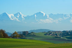 Autumn farmland mountains. Rolling fields and buildings in the fall, against a chain of snow-covered mountains stock images