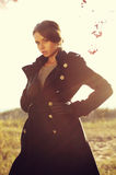 Autumn fashion. Young female in black coat posing in the field with backlit Stock Photos
