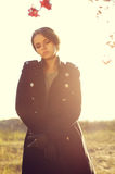 Autumn fashion. Young female in black coat posing in the field with backlit Royalty Free Stock Images