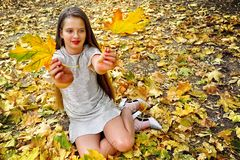 Autumn fashion dress child girl sitting fall leaves park outdoor. royalty free stock photo