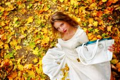Autumn fashion dress woman sitting fall leaves city park outdoor. royalty free stock photos