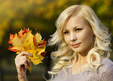 Autumn Fashion Girl. Blonde beautiful young woman with yellow maple leaves in hand. Outside. Fall Royalty Free Stock Photography