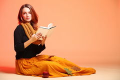 Autumn fashion girl with book orange eye-lashes. Fall. Fashion woman in autumn color student girl in full length with book long false orange eye-lashes Stock Images