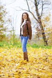 Autumn fashion image of young woman walking in the park Stock Images