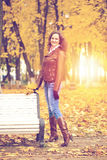 Autumn fashion image of young woman walking in the park. Wearing leather jacket and blue jeans Stock Images