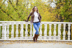 Autumn fashion image of young woman walking in the park. Wearing leather jacket and blue jeans Stock Photo