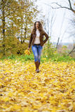 Autumn fashion image of young woman walking in the park. Wearing leather jacket and blue jeans Royalty Free Stock Photo
