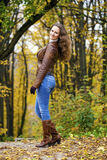 Autumn fashion image of young woman walking in the park. Wearing leather jacket and blue jeans Stock Photos