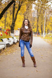Autumn fashion image of young woman walking in the park. Wearing leather jacket and blue jeans Stock Photography