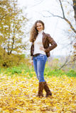 Autumn fashion image of young woman walking in the park. Wearing leather jacket and blue jeans Royalty Free Stock Images