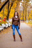 Autumn fashion image of young woman walking in the park. Wearing leather jacket and blue jeans Royalty Free Stock Photography