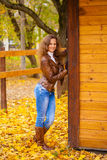 Autumn fashion image of young woman walking in the park. Wearing leather jacket and blue jeans Royalty Free Stock Image