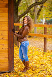 Autumn fashion image of young woman walking in the park. Wearing leather jacket and blue jeans Stock Image