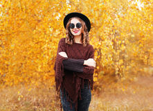 Autumn fashion portrait pretty smiling woman wearing black hat sunglasses and knitted poncho over yellow leaves Stock Photos