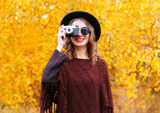 Autumn fashion portrait smiling woman with retro vintage camera wearing black hat sunglasses and knitted poncho over sunny yellow Royalty Free Stock Photos