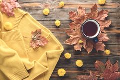 Autumn fashion seasonal concept sweater cardigan cup hot black tea. Autumn fashion seasonal concept, yellow warm soft comfortable sweater cardigan cup hot black stock photography