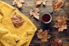 Autumn fashion seasonal concept sweater cardigan cup hot black tea. Autumn fashion seasonal concept, yellow warm soft comfortable sweater cardigan cup hot black royalty free stock photo