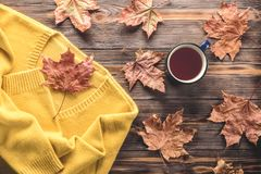 Autumn fashion seasonal concept sweater cardigan cup hot black tea. Autumn fashion seasonal concept, yellow warm soft comfortable sweater cardigan cup hot black royalty free stock image