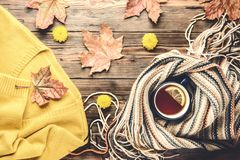 Autumn fashion seasonal concept sweater cardigan Scandinavian knitted scarf cup hot black tea. Autumn fashion seasonal concept yellow warm soft sweater cardigan royalty free stock image
