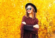 Autumn fashion smiling woman in black round hat, knitted poncho. On a yellow leaves background royalty free stock photography