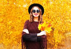 Autumn fashion smiling woman in black round hat, knitted poncho. On a sunny yellow leaves background stock photo