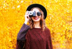Autumn fashion smiling woman with retro camera in black round hat. Knitted poncho stock images