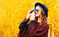 Autumn fashion smiling woman with retro camera in black round hat, knitted poncho. Over sunny yellow leaves background profile view stock photos